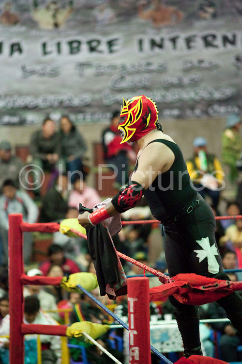 Male wrestler in mask, in ring celebrating signalling to crowd. Lucha Libre wrestling origniated in Mexico, but is popular in other latin Amercian countries, including in La Paz / El Alto, Bolivia. Male and female fighters participate in the theatrical staged fights to an adoring crowd of locals and foreigners alike.