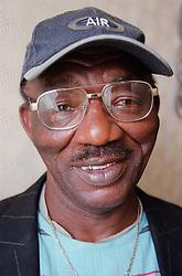 Portrait of man wearing baseball cap and glasses smiling,