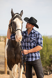 rugged cowboy enjoying time with his horse on a ranch