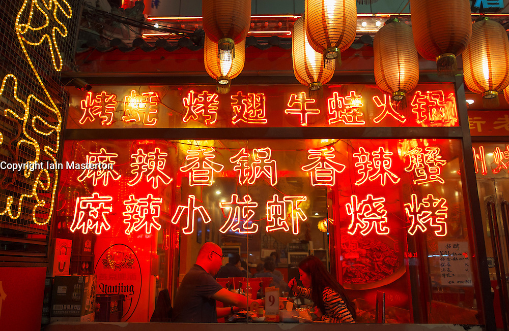 View into restaurant with many lanterns and red neon signs on Ghost Street in Dongzhimen Beijing China