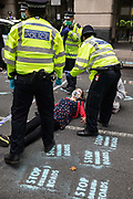 Metropolitan Police officers issue warnings to climate activists from Extinction Rebellion, some of whom wearing hazmat suits, who had occupied the street outside the Department of Transport in protest against roadbuilding on 3 September 2020 in London, United Kingdom. Extinction Rebellion activists are attending a series of September Rebellion protests around the UK to call on politicians to back the Climate and Ecological Emergency Bill CEE Bill which requires, among other measures, a serious plan to deal with the UK's share of emissions and to halt critical rises in global temperatures and for ordinary people to be involved in future environmental planning by means of a Citizens' Assembly.