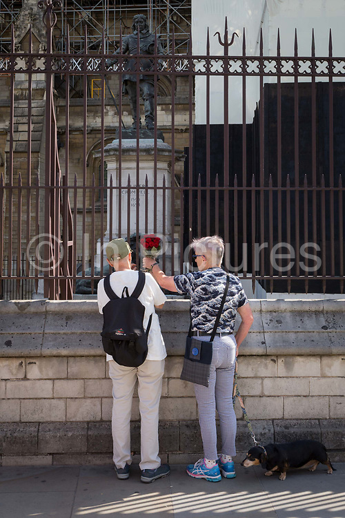 One day after British Prime Minister Boris Johnson successfully asked the Queen to suspend prorogue Parliament in order to manoeuvre his Brexit deal with the EU in Brussels, red roses are left attached by two Remainers at the railings of the Houses of Parliament where the statue of English Civil War military and political leader, Oliver Cromwell stands on 29th August 2019, in Westminster, London, England.
