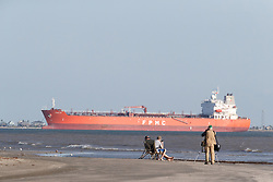 Photographer on beach with ship in channel, Gulf of Mexico, East Beach, Galveston, Texas, USA