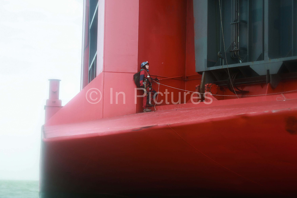 A Greenpeace climber on the back of cargo ship September 21st 2017, Thames Estuary, Kent, United Kingdom. Greenpeace volunteers in kayaks, speed boats and climbers on the jetty prevent the 23,498-tonne cargo ship Elbe Highway from docking at Sheerness in Kent.  The cargo ship is bringing Volkswagen diesel cars into the UK and the Greenpeace action is to prevent this from happening and to make VW ditch diesel. Two climbers board the ship and hang a banner on the roll-on roll-off part of the ship preventing any cars from being off-loaded. The action is part of a long running Greenpeace campaign to curb diesel emmissions and air pollution broght on by diesel cars.