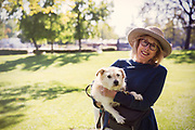 Older woman holding dog in park