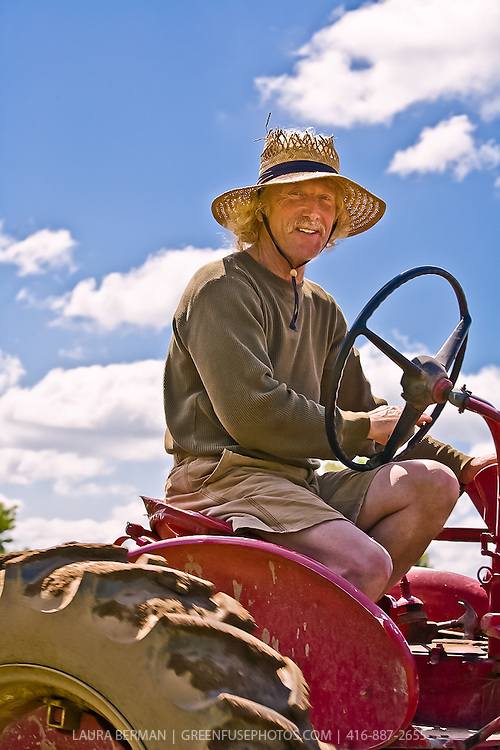 Farmer Ted Thorpe sitting on a red tractor against a bright blue sky.