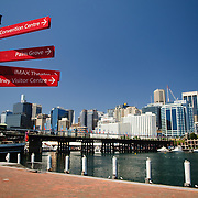 Red signs in Darling Harbour with the Sydney city skyline in the background