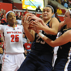 Notre Dame Fighting Irish guard Kayla McBride (23) and guard Brittany Mallory (22) grab a rebound away from Rutgers Scarlet Knights guard Briyona Canty (25) during second half NCAA Big East women's basketball action between Notre Dame and Rutgers at the Louis Brown Athletic Center. Notre Dame defeated Rutgers 71-41.