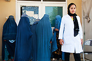 Afghanistan. Mazar-e-Sharif maternity hospital. Woman doctor standing next to patients in blue burqas at the entrance.