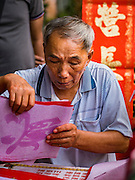 "18 JANUARY 2017 - BANGKOK, THAILAND: A Chinese calligrapher wraps up pieces of Chinese New Year calligraphy for a customer in Bangkok's Chinatown district, before the celebration of the Lunar New Year. Chinese New Year, also called Lunar New Year or Tet (in Vietnamese communities) starts Saturday, 28 January. The coming year will be the ""Year of the Rooster."" Thailand has the largest overseas Chinese population in the world; about 14 percent of Thais are of Chinese ancestry and some Chinese holidays, especially Chinese New Year, are widely celebrated in Thailand.       PHOTO BY JACK KURTZ"