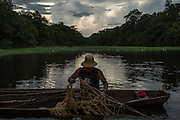 Maraã, Brazil - October 29, 2014: A fisherman unrolls the fishing net back to Lago do Macaco, or Monkey's Lake, while fishing pirarucu in Maraã, western Amazon region. CREDIT: Photo by Mauricio Lima for The New York Times