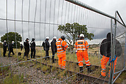 National Eviction Team enforcement agents and security guards watch tree surgeons working on behalf of HS2 Ltd fell a 200-year-old oak tree alongside the East West Rail route known locally as the '7 Sisters Oak' as part of works connected to the HS2 high-speed rail link on 23 September 2020 in Steeple Claydon, United Kingdom. A small group of local people and anti-HS2 activists based at the nearby Poors Piece Conservation Project also observed the felling of the tree, which was home to bats and other species, whilst monitored by a joint force of around fifty bailiffs, security guards and police officers from Thames Valley Police.