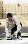A government construction worker poses for a portrait as he cuts a pavement marble stone, in front of the House of Government building. Azeri GDP grew 41.7% in the first quarter of 2007, possibly the highest of any nation worldwide, as the country economy completed its post-Soviet transition into a major oil based economy.<br /> Baku was awarded the right to host of the first European Games, a multi-sport event, and since then the city landscape changed dramatically.