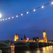 The Palace of Westminster lit up at night in the background, with Westminster Bridge spanning the Thames in the middle, and a string of lights and a street light in the foreground. Taken at night. Includes copyspace.