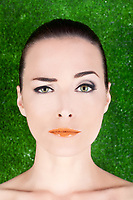Closeup portrait of a beautiful woman with green eyes raising an eyebrow in studio against green
