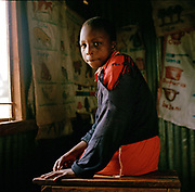 Lucy (13 ) photographed in one of the classrooms at Attnas Kandie School.<br /> She collects rubbish when she's not at school. She is one of five children – the eldest is at college but the other siblings help to support him by sorting rubbish. Lucy's mum sometimes washes clothes for other people but is sick and can't often earn enough to feed the children. Lucy is now in primary school and gets lunch there every day thanks to Mary's Meals.<br /> <br /> <br /> Making a living from collecting rubbish is no easy job; disease, injury, substance abuse and even the threat of violence is an everyday reality for the people who live and work at the dumps in Eldoret.  It's especially hard for the mothers and their children forced through poverty to scrape a living of around $1 dollar a day.
