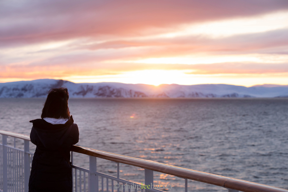 Woman on deck looking at scenic winter landscape at sunrise, Havoysund, Norway