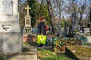 A lady with plastic bag and a trolley walks over Rakowicki cemetery in Krakow, Poland 2019.