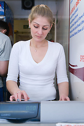 Bulgarian woman owner of fish and chip shop using the till,