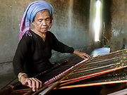 An elderly Hindu Cham woman weaves cotton and silk fabric on a back-strap loom at home in My Nghiep village, Ninh Thuan province, Central Vietnam.  The resulting fabric is used to make the traditional sarong style skirt worn by Cham women on special occasions or sold to local customers in the village. The Cham people are remnants of the Kingdom of Champa (7th to 18th centuries) and are recognised by the government as one of Vietnam's 54 ethnic groups.