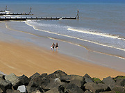 Family walking sandy beach at Sheringham, Norfolk, England, UK
