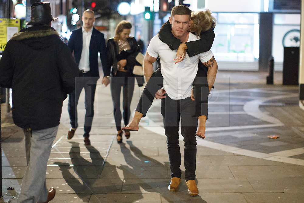 """© licensed to London News Pictures. London, UK 14/12/2013. A """"Mad Friday"""" reveller carries his drunk partner in Soho, London whilst enjoying the last Friday night out before Christmas, which is also the busiest night of the year for emergency services. Photo credit: Tolga Akmen/LNP"""