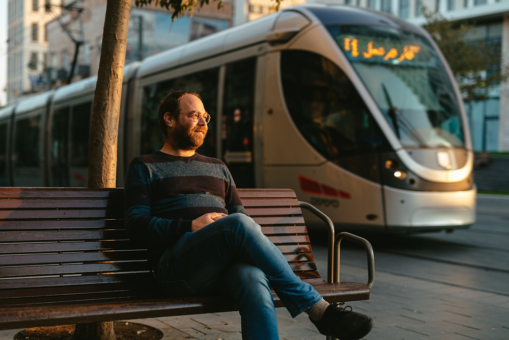 Avi Tfilinski, 42, a former ultra-Orthodox Jewish man that has left the strict Jewish religious community in which he lived for most of his life, poses for a portrait in central Jerusalem, Israel, on November 24, 2019, as the Jerusalem light-rail passes in the background. Avi Tfilinski is a client of Hillel - The Right to Choose, an Israeli non-profit organization dedicated to helping young adults who have left the ultra-Orthodox Jewish world integrate and lead successful lives as members of secular Israeli society.