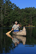 Jack Gribble, of Barnes, Wisconsin, paddles his homemade birchbark canoe on the Eau Claire River, with his dog Cider.