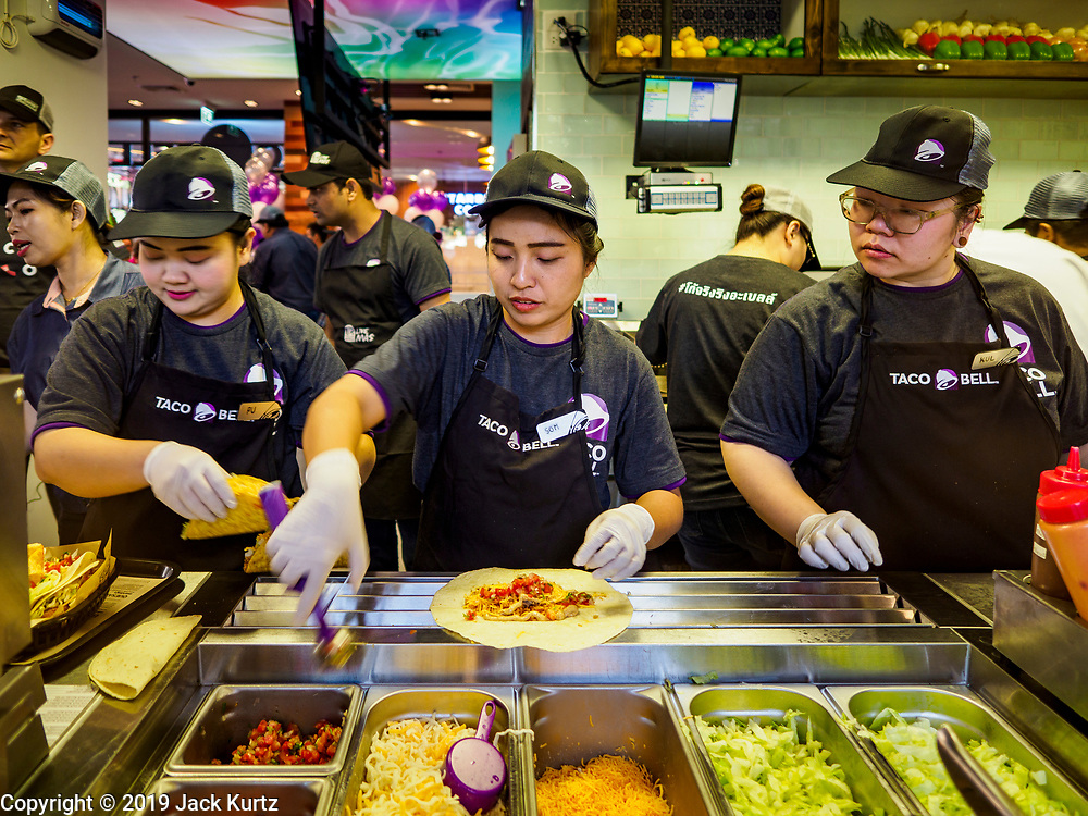 24 JANUARY 2019 - BANGKOK, THAILAND:  Taco Bell works prepare a customer's order during the grand opening of the first Taco Bell in Thailand. The restaurant has a 215 square meter space in the Mercury Ville, a mixed use retail/office building in central Bangkok. Taco Bell is owned by Yum Brands, which also owns KFC, Pizza Hut, and WingStreet. Taco Bell in Thailand joins KFC, which has more than 500 restaurants in Thailand and Pizza Hut, which recently started expanding in Thailand.   PHOTO BY JACK KURTZ