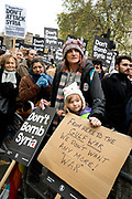 Whitehall November 28th Protest organised by Stop the War against the proposed bombing of Syria. A parent and child hold a home-made cardboard sign saying 'From here to the Gulf War , we don't want any more 'War'.