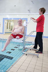 Disabled man; with the assistance of a member of staff; being lowered into swimming pool using a portable aquatic lift at his sports leisure centre,