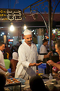 A chef takes payment for food at a stall in the Djemaa el Fna in the medina of Marrakech, Morocco. Every night the main square fills with dozens of food vendors and their carts.