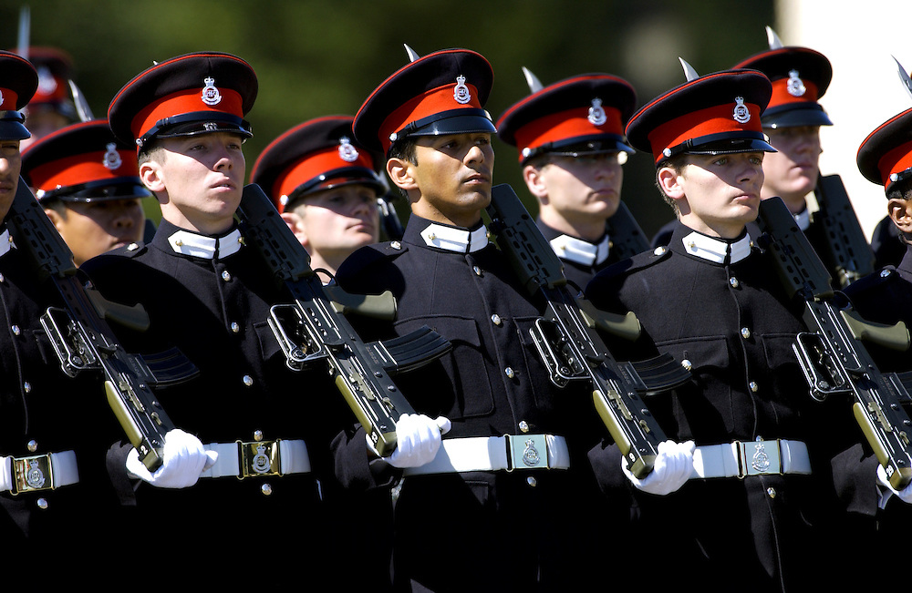 Soldiers in military dress uniform with rifles on parade at Sandhurst Royal Military Academy, Surrey, England