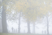 On the first morning of the government's second national Coronavirus lockdown, Londoners walk through morning fog which obscures the landscape in Ruskin Park, a south London green space, on 5th November 2020, in London, England.