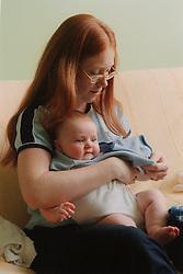 Teenage mother dressing baby,