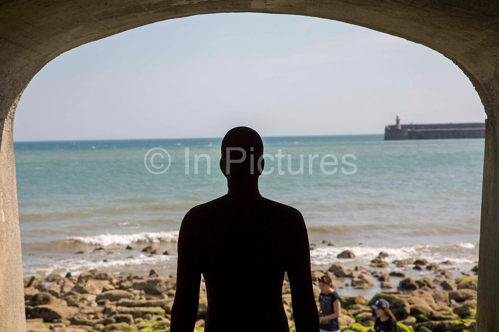 An Antony Gormley cast iron figure from the series 'Another Time' located in the arches of Sunny Sands Bay sea defence. Part of the 2017 Folkestone Triennial. Folkestone, Kent.