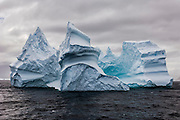 A majestic iceberg sculpted by the weather and ocean looms in front of a stormy sky, South Orkney Islands, Scotia Sea