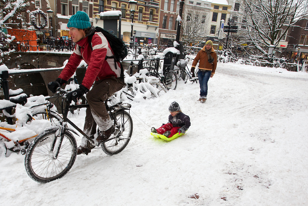 Een man fietst met een slee achter zich aan over de Oudegracht in Utrecht.<br /> <br /> A man is towing a sled with his bike at the Oudegracht in Utrecht.