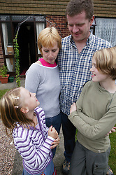 Family standing outside house together,