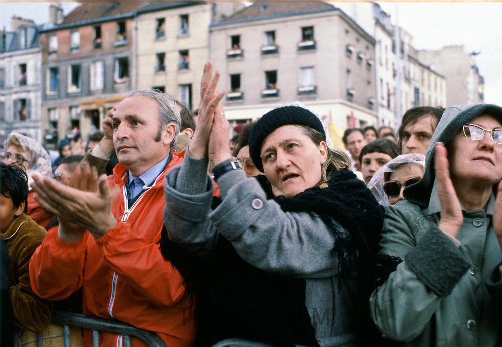 Pilgrims in crowd applaud Pope John Paul II during his visit to Paris, France