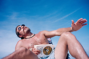 Man reading Edward Abbey's 'The Brave Cowboy' on the beach.