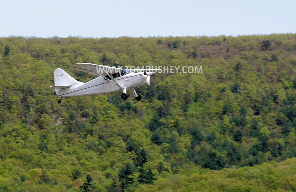 Wurtsboro, NY - A 1947 Stinson airplane takes off from Wurtsboro Airport on May 11, 2008. The airport celebrated its grand reopening with a fly in.