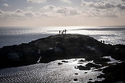 Walkers reach a hill top along a trail path in Holyhead Breakwater Country Park on the coast of Holyhead, on 20th February 2020 in Anglesey, North Wales, United Kingdom. The country park opened in 1990 and is on the site of an old stone quarry.