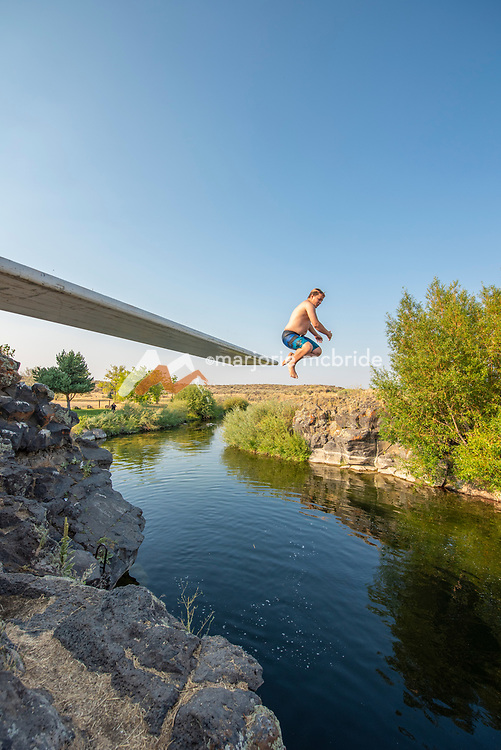 Young boy having fun and jumping from the Ledges swimming hole in Richfield, Idaho.