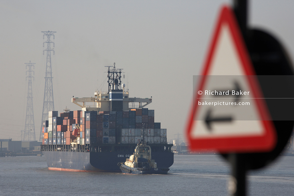 A giant cargo container ship on a wide section of the River Thames eases upstream towards Tilbury Docks.