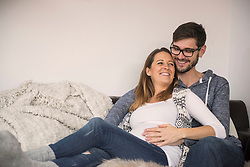 Pregnant woman on sofa with her husband, Munich, Germany