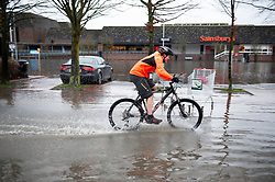 ©Licensed to London News Pictures 22/12/2019. <br /> Tonbridge ,UK. Mountain biker enjoying the water. Heavy rain over night has caused more Christmas flooding in Kent.  Christmas shoppers in Tonbridge, Kent are facing severe disruption in the town centre with two car parks, roads and pathways all flooded and out of action as the River Medway bursts its banks. Photo credit: Grant Falvey/LNP