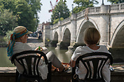 Two elderly ladies sit in the shade along Richmond riverside as record temperatures soar across England on the 25th July 2019 in Richmond in the United Kingdom. The Met Office has estimated that parts of England could reach a record-breaking 39C this afternoon.