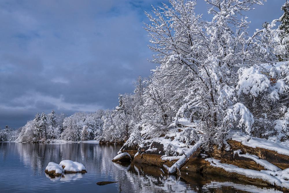 Heavy fresh snow on shoreline trees & rocks in winter, Lee, MA