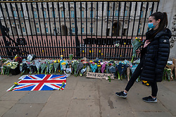 © Licensed to London News Pictures. 09/04/2021. LONDON, UK. A well wisher prepares to lay flowers outside Buckingham Palace after the death of Prince Philip, aged 99, was announced.  Photo credit: Stephen Chung/LNP
